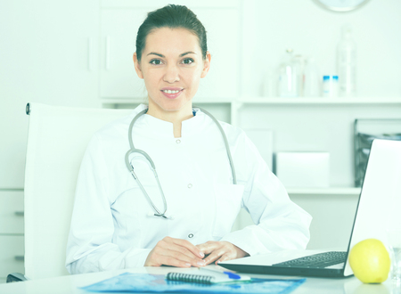 Photo pour Smiling woman doctor working effectively in her office - image libre de droit