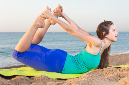 Photo pour Woman in blue T-shirt is practicing stretching on the beach. - image libre de droit