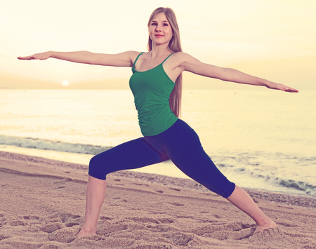 Photo for Female 20-25 years old is doing excercises on endurance on the beach near sea. - Royalty Free Image