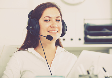 Photo pour Young female worker productively operating at call-center - image libre de droit
