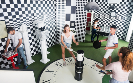 Foto de Smiling young people trying to find solution of conundrum in closed space of lost room - Imagen libre de derechos