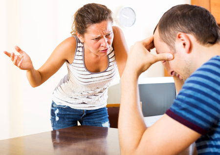 Photo pour Young couple quarrels sitting at the table at home - image libre de droit