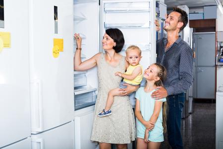 Foto de smiling family with two children choosing modern fridge in household store - Imagen libre de derechos