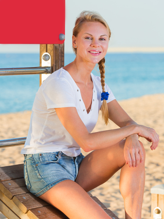Photo for Active woman in white T-shirt is resting after training on the beach - Royalty Free Image