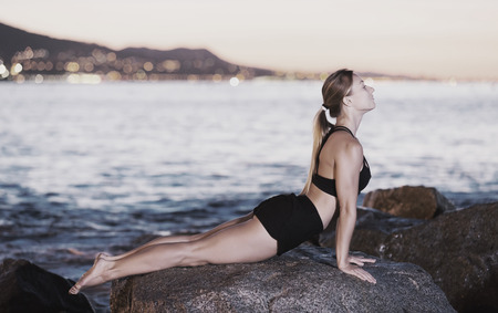 Photo pour Young woman is practicing stretching on a rock near sea at the dawn. - image libre de droit