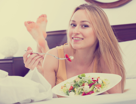 cheerful woman in lingerie having a salad while laying in the bed