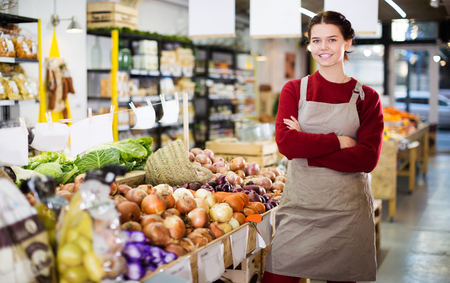 Photo for Smiling young saleswoman offering large onion in vegetable section of foodshop - Royalty Free Image