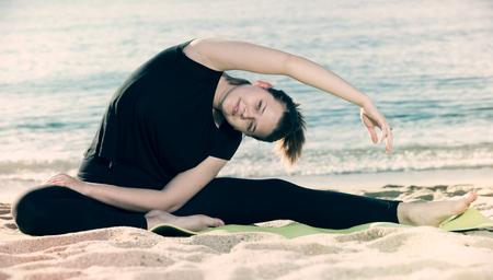Photo for Female in black T-shirt is practicing asana on the beach. - Royalty Free Image