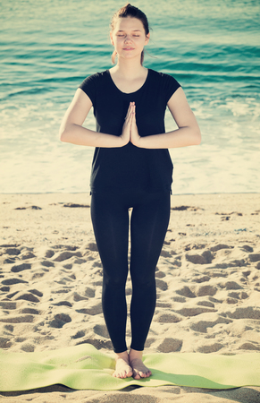 Photo pour Female in black T-shirt is staying and practicing meditation on the beach. - image libre de droit