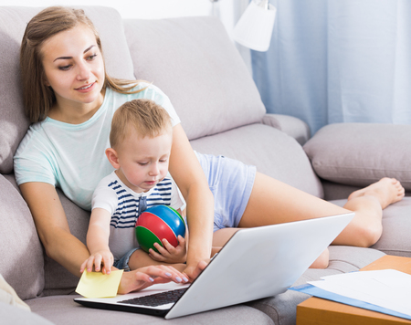 Photo pour Satisfied woman with child is productively working behind laptop at home. - image libre de droit