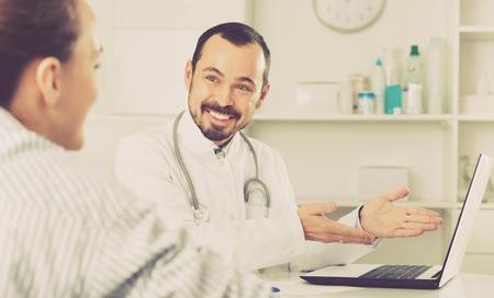 Foto de Pleasant cheerful positive woman having consultation with male doctor in hospital - Imagen libre de derechos