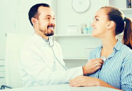 Foto de Smiling male doctor consultation woman patient in medicine center - Imagen libre de derechos
