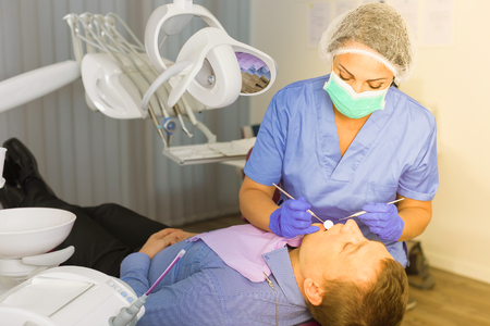 Foto de dentist professional filling teeth for man patient sitting in medical chair - Imagen libre de derechos