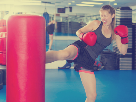 Photo pour Portrait of active woman practicing with punching bag in box gym - image libre de droit