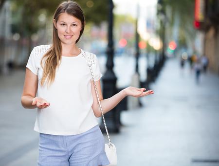 Foto de Smiling friendly girl inviting you to walk around summer city - Imagen libre de derechos