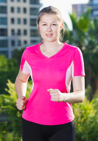Photo pour Adult woman in pink T-shirt is jogging around the urban. - image libre de droit