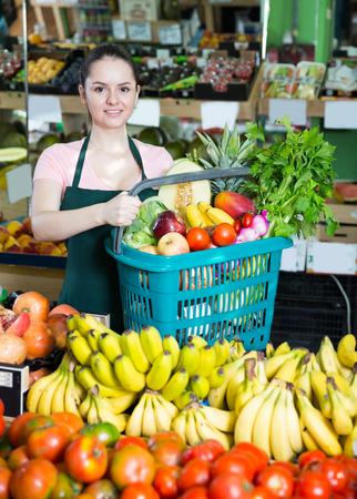 Photo for Positive salesgirlr with range of vegetables and fruits in shopping basket  - Royalty Free Image