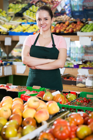 Photo for Smiling female grocery worker in apron near shelves of fruits and vegetables - Royalty Free Image