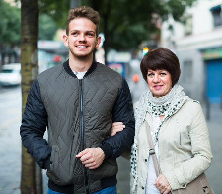 Foto de Mother with glad son in casual clothes walking through ancient European city - Imagen libre de derechos
