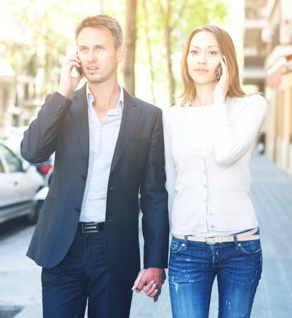 Foto de Indifferent girl and guy speaking on phones while walking together - Imagen libre de derechos