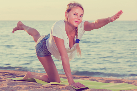 Photo for Smiling adult woman in white T-shirt is doing excercises on endurance on the beach. - Royalty Free Image