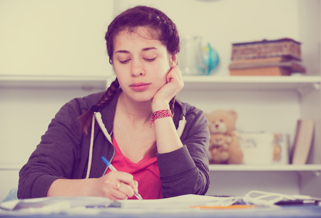 Photo pour Young female student studying productively alone at home - image libre de droit