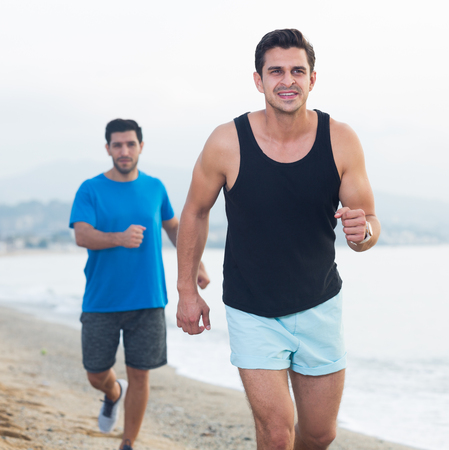 Photo for Adult men are jogging together on the beach near ocean. - Royalty Free Image
