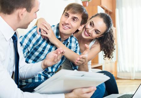 Foto de happy couple and banking agent discussing possibility of mortgage - Imagen libre de derechos