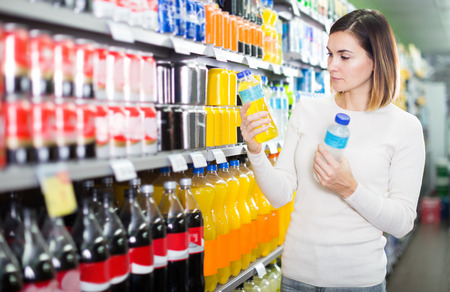 Photo for Girl customer looking for refreshing beverages in a supermarket  - Royalty Free Image