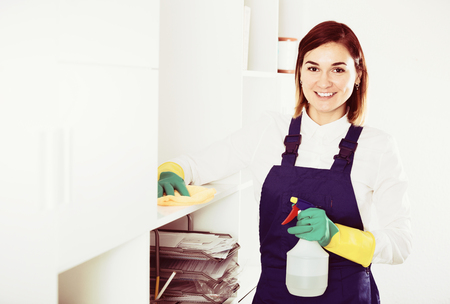 Photo pour Young female cleaner working productively on task in office - image libre de droit