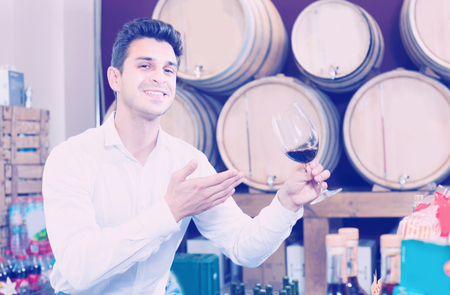 Foto de Happy man customer holding glass of red wine and tasting in winery section in shop - Imagen libre de derechos