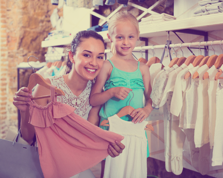 Foto de Young cheerful woman with small girl choosing white baby clothes in kids apparel boutique - Imagen libre de derechos