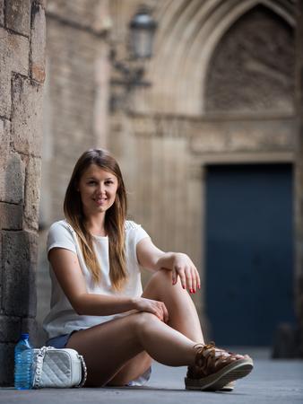 Foto de Smiling young woman sitting near old stone cathedral wall  - Imagen libre de derechos