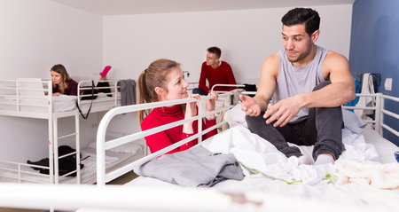 Photo pour Attractive girl talking to smiling man who sitting on top bunk of bunk bed in hostel  - image libre de droit