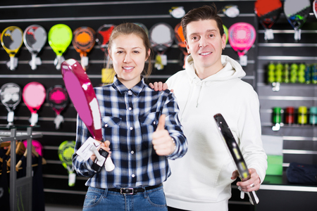 Sporty couple is demonstraiting modern racket for padel in the store.