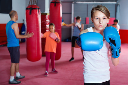 Photo for Portrait of young diligent serious positive boy boxer wearing gloves at boxing hall - Royalty Free Image