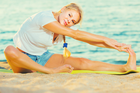 Photo pour Female 20-30 years old is practicing stretching  in white T-shirt on the beach near sea. - image libre de droit