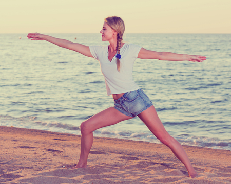 Photo pour Smiling adult woman in white T-shirt is doing excercises on endurance on the beach. - image libre de droit