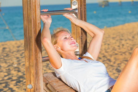 Photo pour Smiling adult woman in white T-shirt is doing excercises on strenght on the beach. - image libre de droit