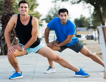 Photo for Portrait of two male friends who are stretching in the park near beach - Royalty Free Image