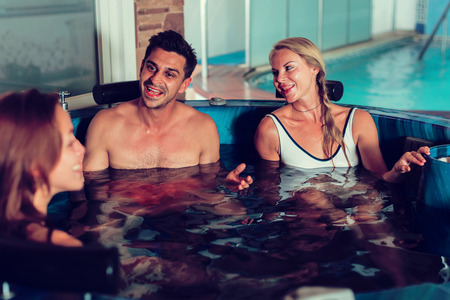 Photo for Man with two girlfriends are enjoying of relax together in pool in spa. - Royalty Free Image