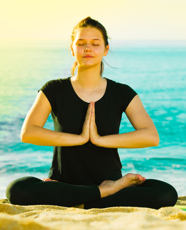 Photo pour Girl in black T-shirt is sitting and practicing yoga on the beach. - image libre de droit