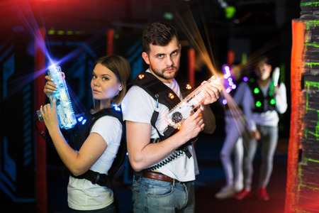 Photo for Two confident laser tag players standing back to back with guns on gaming arena in bright beams of laser gun  - Royalty Free Image