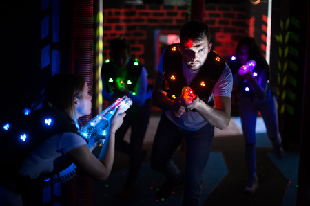Photo for Emotional guy with laser pistol playing laser tag with friends on dark labyrinth - Royalty Free Image