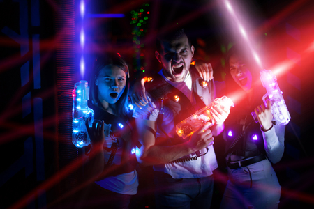 Foto de Group portrait of young people in colorful beams of laser guns having fun on lasertag arena - Imagen libre de derechos