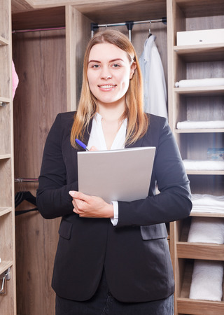 Photo for Portrait of young successful woman sales manager in furniture salon, standing with clipboard in interior of dressing room - Royalty Free Image
