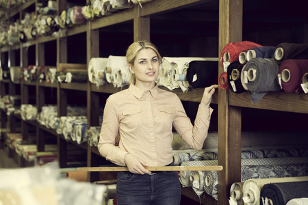 Photo for Portrait of positive salesgirl working in fabric store, demonstrating wide range of stylish cloth - Royalty Free Image
