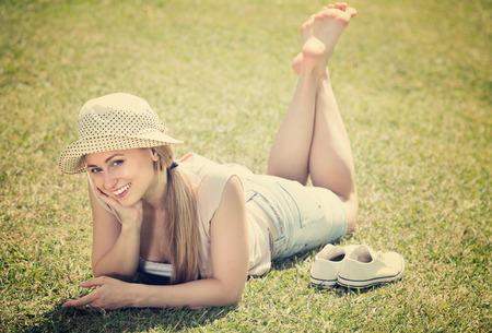 Foto de joyful  smiling barefoot girl lying on green grass in park on sunny day  - Imagen libre de derechos