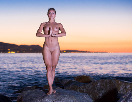 Photo for Young nude female is standing on a rock near the sea at the dawn. - Royalty Free Image