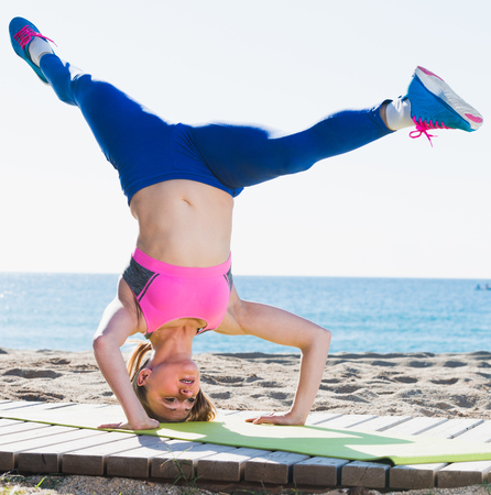 Photo pour Woman 28-35 years old is practicing stretching on the beach near sea.  - image libre de droit